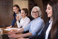 Усмехаясь коллеги представляя совместно на рабочем месте Стоковая Фотография RF
