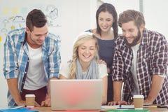 Усмехаясь коллеги работая на компьтер-книжке Стоковая Фотография RF