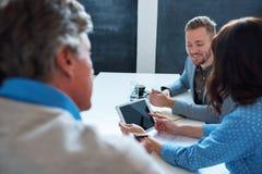 Усмехаясь коллеги работая с цифровой таблеткой в офисе Стоковая Фотография RF