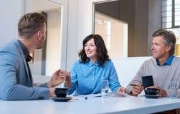3 усмехаясь коллеги работы говоря дело совместно в офисе Стоковая Фотография