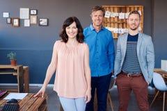 Усмехаясь коллеги работы стоя совместно в современном офисе Стоковое Изображение