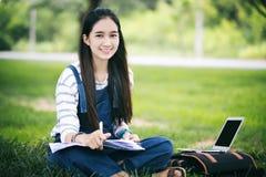Усмехаясь красивая азиатская книга и деятельность чтения девушки на дереве дальше Стоковое Изображение RF
