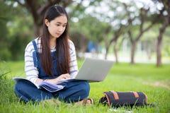 Усмехаясь красивая азиатская книга и деятельность чтения девушки на дереве дальше Стоковые Изображения RF