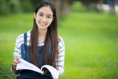 Усмехаясь красивая азиатская книга и деятельность чтения девушки на дереве дальше Стоковое фото RF