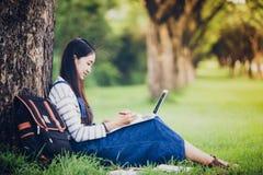 Усмехаясь красивая азиатская книга и деятельность чтения девушки на дереве дальше Стоковая Фотография RF
