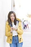 Усмехаясь красивая латинская женщина используя умный телефон в улице стоковое изображение rf