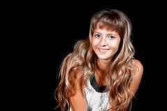 Усмехаясь красивая голубоглазая белокурая девушка в белом платье на черной предпосылке Стоковые Фотографии RF