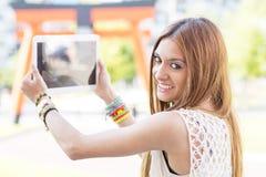 Усмехаясь красивая девушка фотографируя с планшетом в t стоковое фото rf
