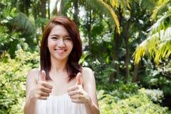 Усмехаясь красивая женщина давая 2 большого пальца руки вверх, горизонтальный формат Стоковое Изображение