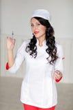 Усмехаясь красивая женщина доктора с красными губами и шприцем в высокой Стоковое Фото