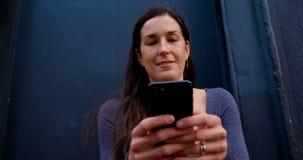 Усмехаясь красивая женщина отправляя SMS на мобильном телефоне 4k акции видеоматериалы