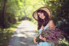 Усмехаясь красивая женщина с полевыми цветками Стоковая Фотография