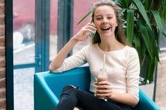 Усмехаясь красивая маленькая девочка говоря на телефоне и выпивая коктеиле на кафе Портрет красивой усмехаясь женщины сидя на a Стоковая Фотография