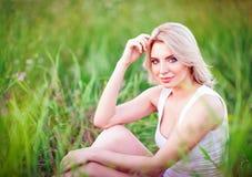 Усмехаясь красивая маленькая девочка сидя среди зеленой травы и цветков Стоковые Изображения RF