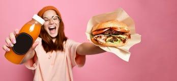 Усмехаясь красивая молодая белокурая модель женщины в гамбургере удерживания ткани hoodie хипстера и соке бутылки стоковые изображения rf