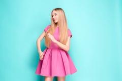 Усмехаясь красивая молодая женщина в розовом мини платье представляя, представляя что-то и смотря прочь Длина 3 четвертей стоковые фото