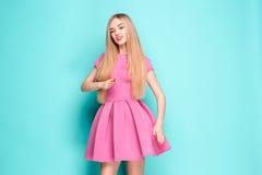 Усмехаясь красивая молодая женщина в розовом мини платье представляя, представляя что-то и смотря прочь Длина 3 четвертей стоковое фото
