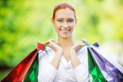 Усмехаясь красивая молодая женщина с покупками Стоковая Фотография