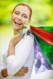 Усмехаясь красивая молодая женщина с покупками Стоковые Изображения