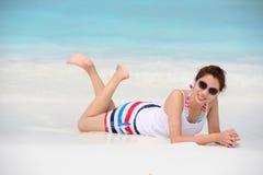 Усмехаясь красивая ложь женщины на пляже лежит на пляже Стоковое Фото