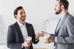усмехаясь красивые бизнесмены говоря во время перерыва на чашку кофе Стоковые Фотографии RF
