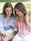 Усмехаясь красивые девушки с мобильным телефоном Стоковые Изображения