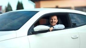 Усмехаясь красивый европейский случайный молодой мужчина представляя усаживание на съемке современного белого роскошного автомоби видеоматериал