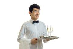 Усмехаясь красивый кельнер при черные волосы и рубашка держа поднос с 2 стеклами вина Стоковая Фотография RF