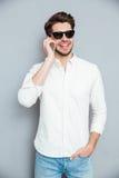Усмехаясь красивый молодой человек в солнечных очках говоря на мобильном телефоне Стоковое Изображение RF