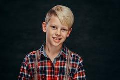 Усмехаясь красивый предназначенный для подростков мальчик нося checkered рубашку с подтяжками стоковое фото