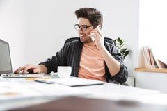 Усмехаясь красивый человек в eyeglasses говоря смартфоном стоковое изображение rf