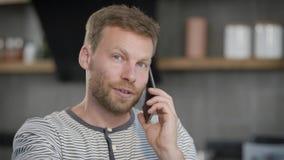 Усмехаясь красивый человек говорит мобильным телефоном сидя в его доме, смотрящ камеру и на стороны видеоматериал