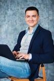 Усмехаясь красивый человек работая на компьютере Стоковая Фотография
