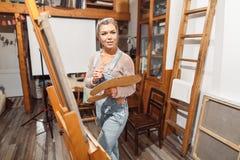 Усмехаясь краски девушки на холсте с цветами масла в мастерской Стоковые Изображения RF