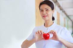 Усмехаясь красное сердце держало путем усмехаясь женская рука ` s медсестры в больнице или клинике здравоохранения Профессионал,  стоковая фотография rf