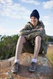 Усмехаясь крышка женщины нося сидя на утесе Стоковая Фотография