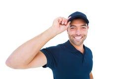 Усмехаясь крышка работника доставляющего покупки на дом нося на белой предпосылке Стоковое фото RF
