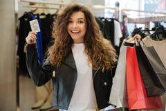 Усмехаясь курчавая молодая дама стоя в одежде ` s женщин ходит по магазинам Стоковое Изображение RF
