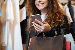 Усмехаясь курчавая молодая дама стоя в одежде ` s женщин ходит по магазинам Стоковое Изображение