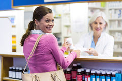 Усмехаясь клиент и аптекарь держа медицину в фармации Стоковые Фотографии RF