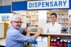 Усмехаясь клиент и аптекарь держа медицину в фармации Стоковая Фотография