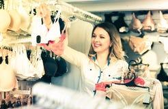 Усмехаясь клиент молодой женщины выбирая бюстгальтеры Стоковые Фото