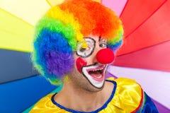 Усмехаясь клоун на красочной предпосылке Стоковые Изображения