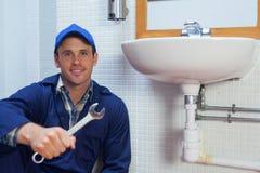 Усмехаясь ключ удерживания водопроводчика сидя рядом с раковиной стоковые изображения