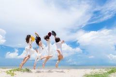 Усмехаясь лето платья моды азиатской женщины группы нося белое идя песочный пляж моря, предпосылка солнечности голубого неба Счас стоковые изображения rf