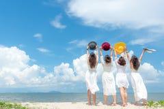 Усмехаясь лето платья моды женщины группы нося белое идя на песочный пляж океана, красивая предпосылка голубого неба стоковая фотография