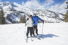 Усмехаясь лыжники катаясь на лыжах совместно на красивой верхней части горы на солнечный день Стоковое фото RF