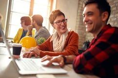 Усмехаясь люди архитектора работая совместно на столе на компьютере Стоковое фото RF