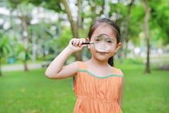 Усмехаясь маленькая азиатская девушка ребенка играя с лупой в зеленом саде стоковое изображение