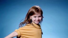 Усмехаясь маленькая девочка в желтый закручивать Голубая предпосылка, супер замедленное движение видеоматериал